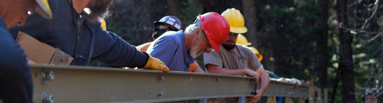 Plusieurs ouvriers du bâtiment travaillent sur une poutre en métal